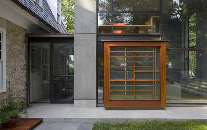 Solid concrete column flanked by entry door to the left and Spanish Cedar Vitrine to the right