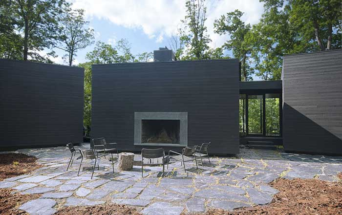 The main glassed Entry is between the right and center volumes. The terrace and fireplace surround are slate from Buckingham slate